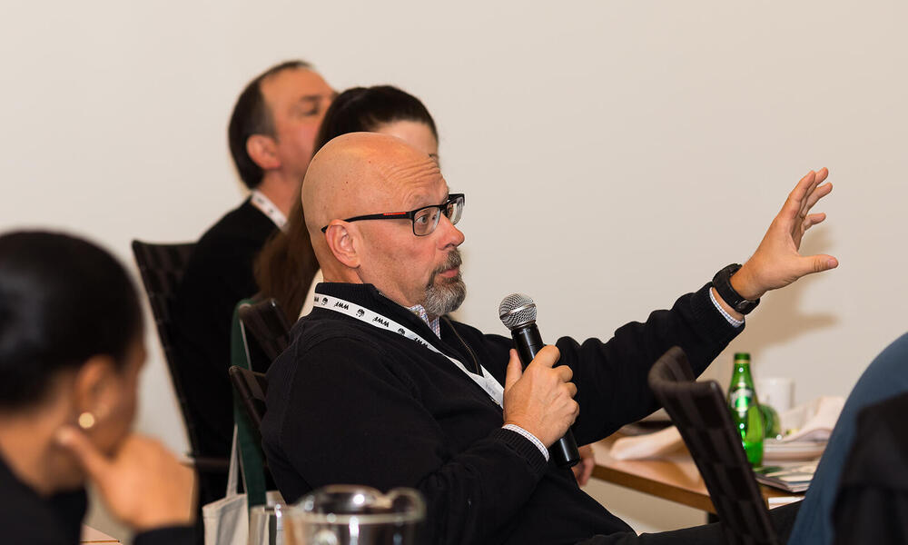 A man with glasses speaks into a microphone at the 2017 Partner Symposium