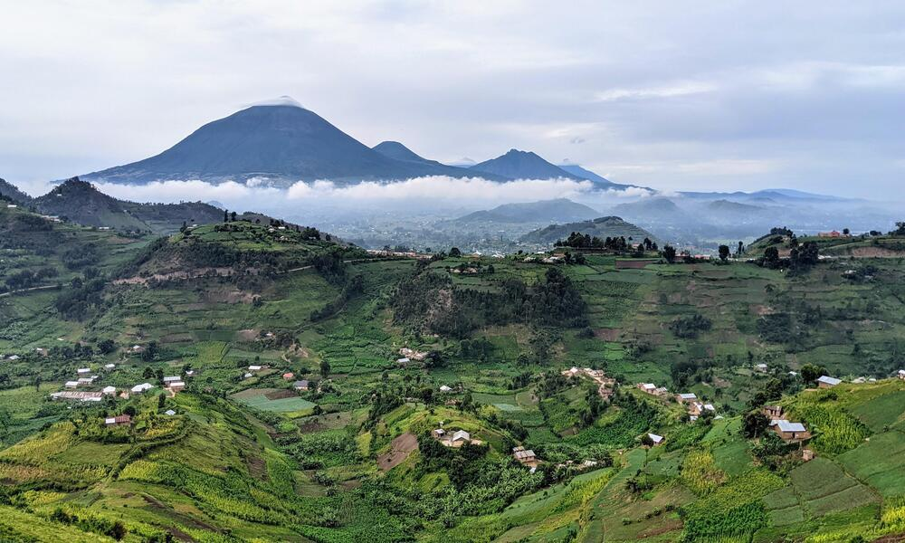 Rolling green hills with homes on them and large cloud-covered mountains in the background