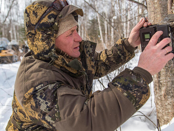 Ranger Andrei Kortjak sets up a camera trap in the snows of Anuiksky National Park, Russia