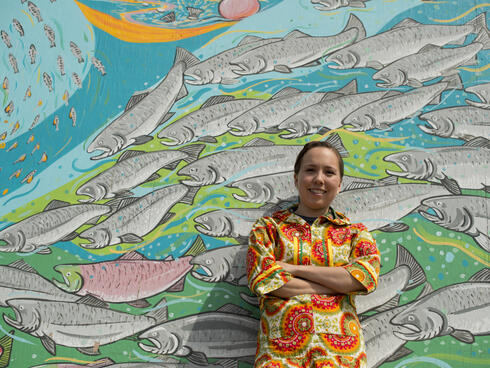 Apayo Moore in front of a mural