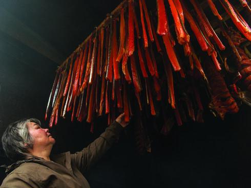 Bristol Bay resident appraises hanging salmon strips
