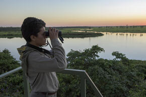 Carolina Alvarez looks out across a river with binoculars at sunset