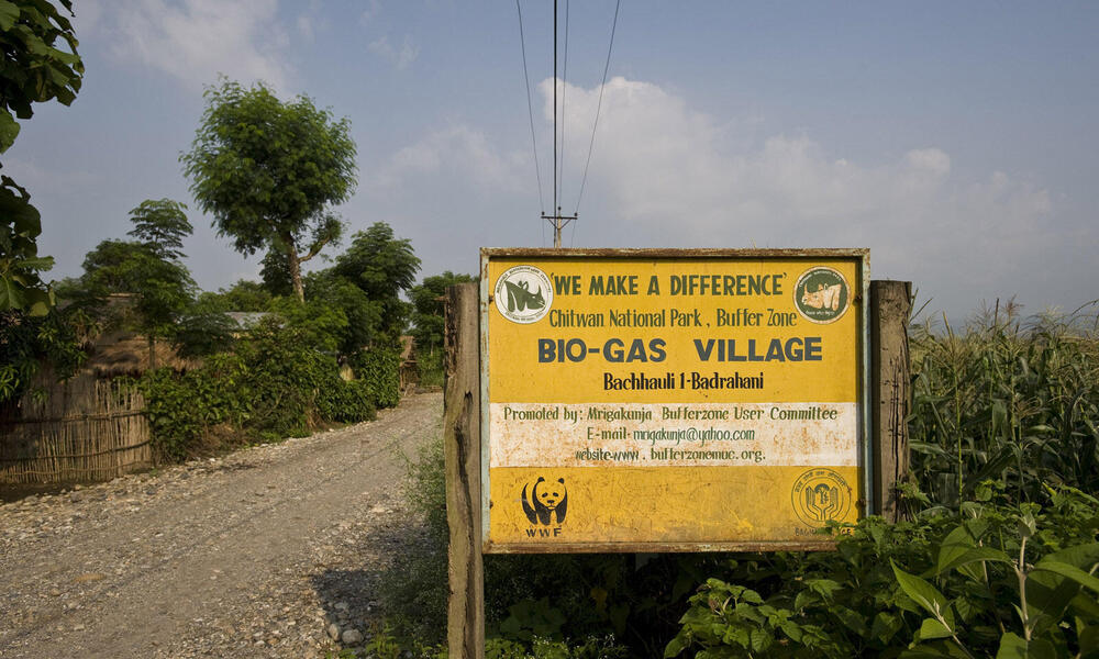 A large sign indicating the Bio-gas village in Chitwan National Park buffer zone. Nearly 90 % of the village had bio gas installed, funded by WWF. Villages used to use firewood for their cooking, but now use bio gas instead. This is not only a cleaner met