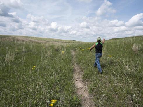 Boy runs through grasslands of his family ranch