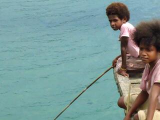 Boys on a dock in Bird's Head Seascape, West Papua, Indonesia