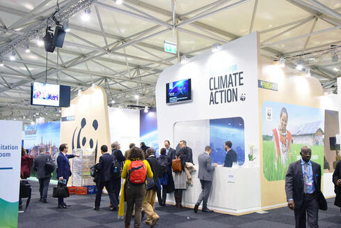 People walk around the Climate Action Center at COP 23