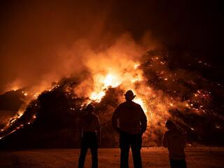 Firefighters fight a large fire burning in the hills.