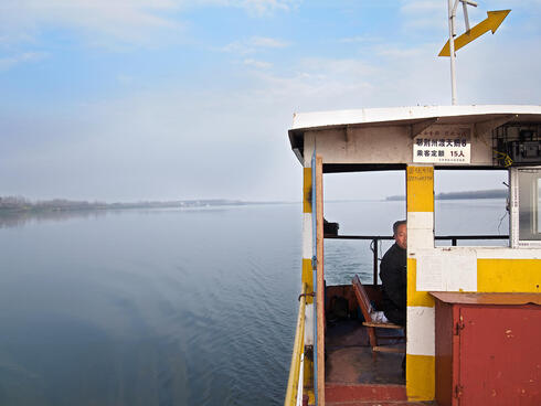 A ferry captain looks for signs of the Yangtze finless porpoise on the Tian-E-Zhou oxbow lake near Yueyang, China