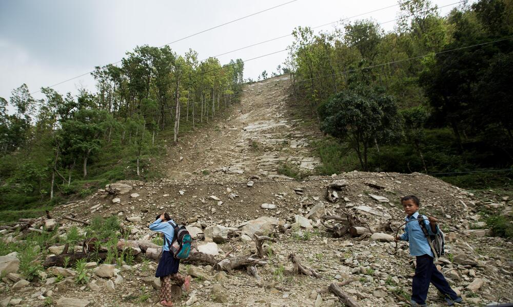 Two children walk in front of a steep dirt slope after a landslide