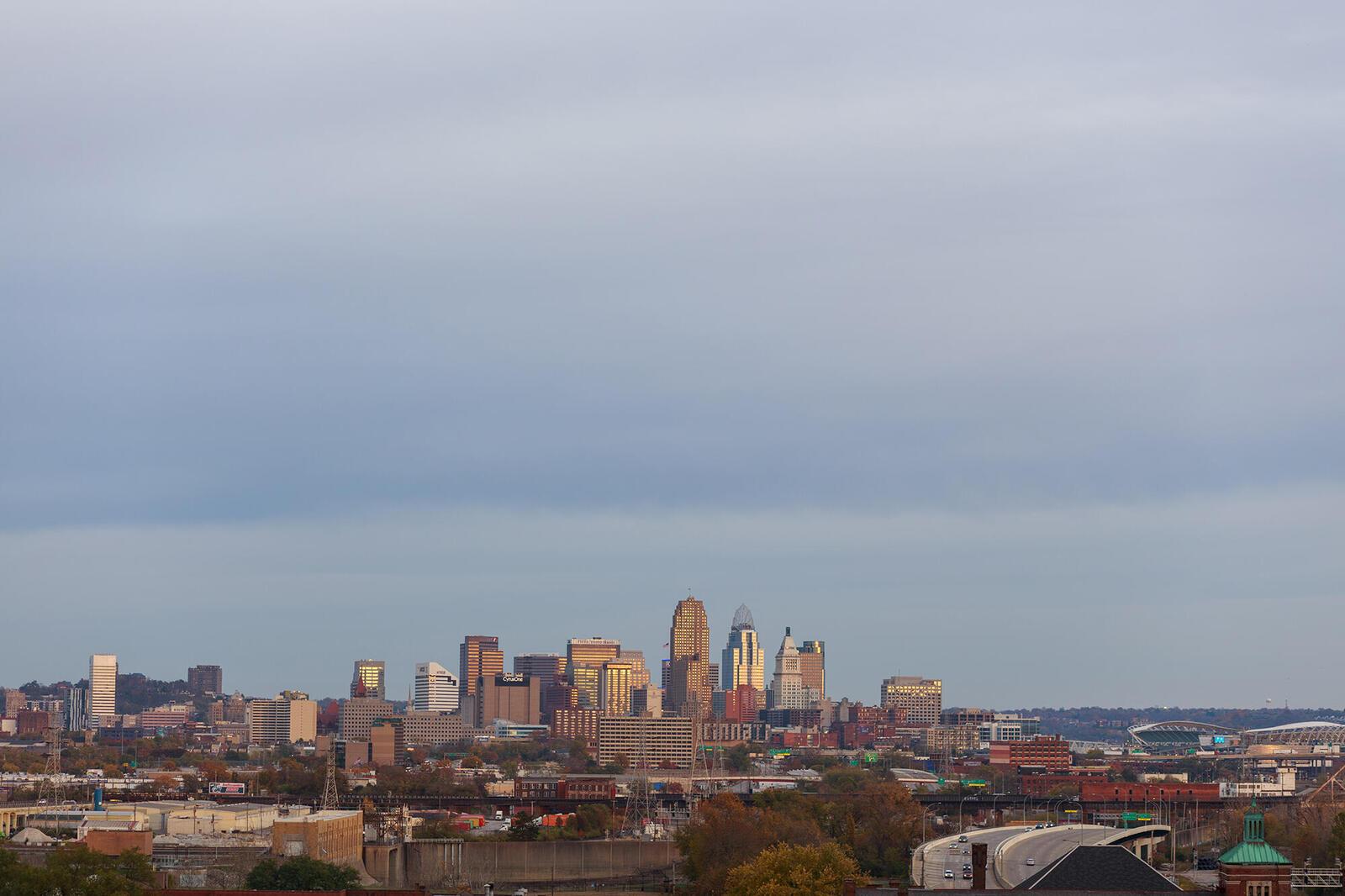 Skyline of the city of Cincinnati against a cloudy sky.