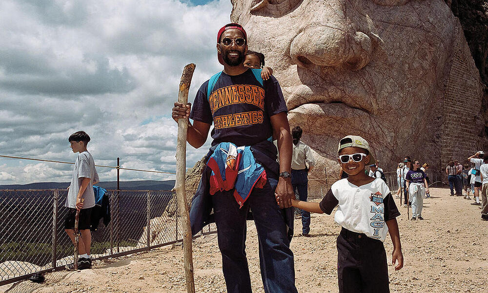A man and his son pose in front of Crazy Horse Memorial