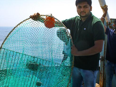 Man stands on board a fishing boat at sea holding a large green fishing net