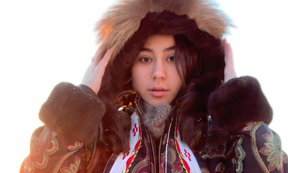 Allie Ivanoff looks straight at the camera in a large parka in the snow