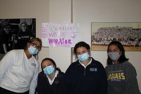 """Students in front of a poster that reads, """"Be a Food Waste Warrior"""""""
