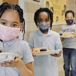students stand in line with trays of food