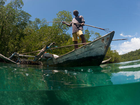 Split level of a shallow coral reef and mangroves with local West Papuan man and his wife in their dugout canoe
