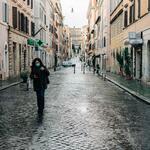 A woman walks down an empty street in a city