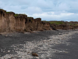 Eroding cliffs along the shoreline of Bristol Bay near the former village of Meshik. The village was completed relocated several miles inland due to coastal erosion in Port Heiden, Alaska, United States.