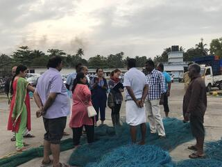 A group of people stand among a pile of blue fishing nets learning about sustainable fishing