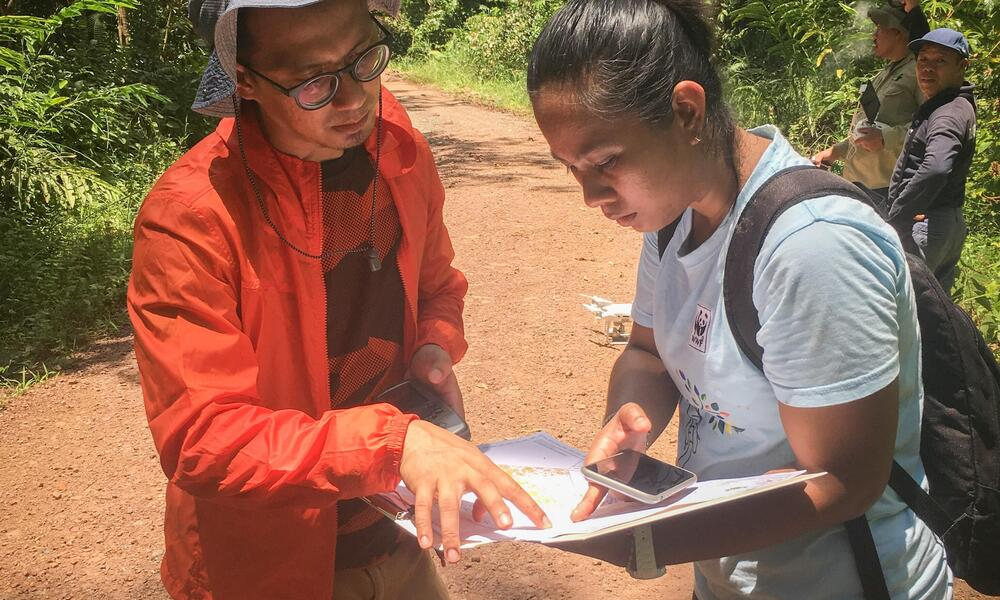 Two researchers stand in a Borneo forest looking over notes on a pad of paper