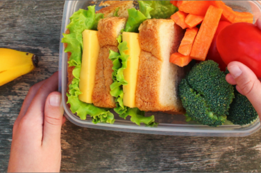 a closeup of a child's lunch with a banana, sandwich and vegetables
