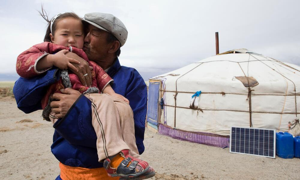 A father holds his young daughter in his arms and kisses her on the cheek in front of a yurt
