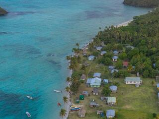 Aerial view of a fishing community along the coast nestled up against clear blue waters