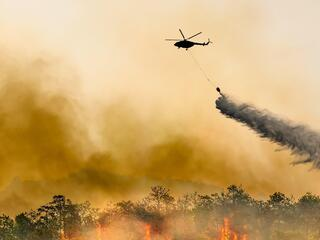 Silhouette of a firefighting helicopter dumps water on a burning forest