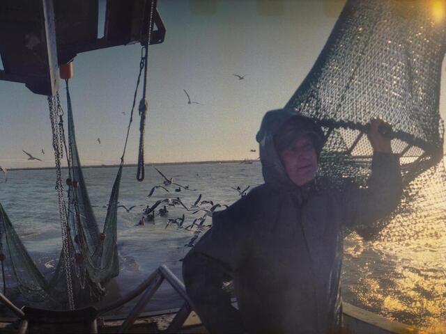 Deckhand Arthur Miller sets nets off the coast of Galveston, Texas