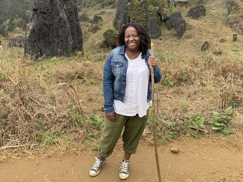 Florence Adewale stands on a trail with a hiking stick in a blue jacket