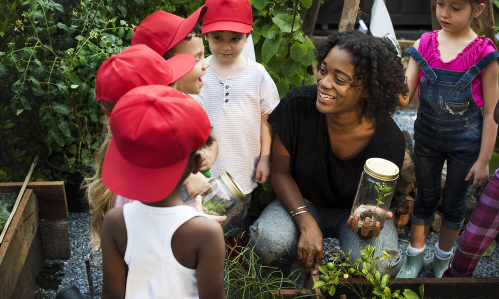 Children gather around a woman holding a plant and smiling