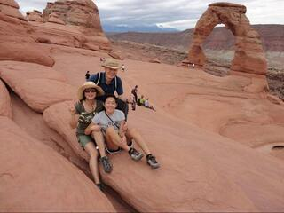 Grace Lee sits in front of her mom and dad at a national park with a huge red arch in the background