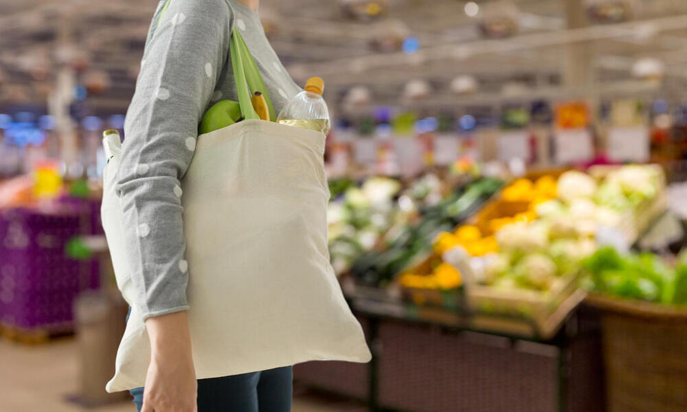 A woman with a beige tote bag walks through the produce section of a grocery store