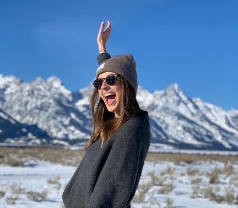 Hannah Miller smiles at the camera on top of snow with a mountain in the background