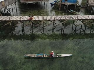Aerial view of a man paddling a skinny blue canoe alongside a tall wooden dock where three small girls sit