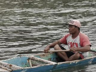 A man in a tshirt and pink baseball cap sits inside a skinny blue canoe on the water