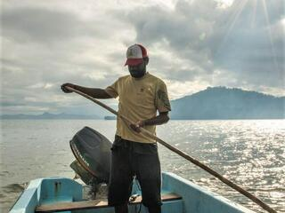 A man in a yellow tshirt and baseball cap stands in a small blue fishing boat holding a long paddle out at sea with the sun shining and a mountain range behind him