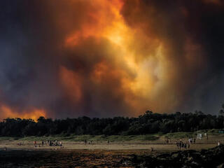 People watch fire and smoke on Broulee Beach, Australia