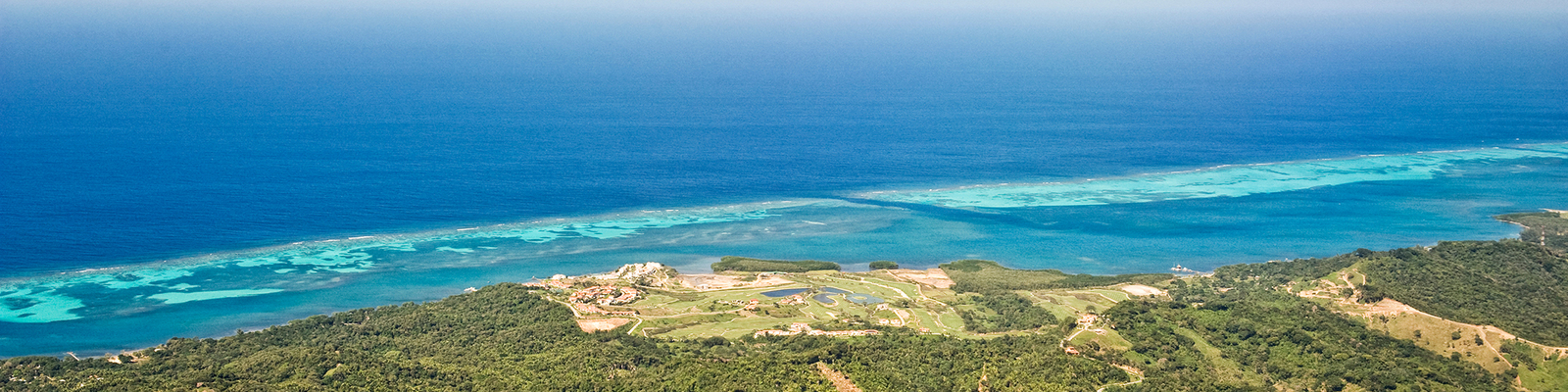 Aerial view of a coastline in Roatan, Bay Islands, Honduras. The ocean is a deep blue. At the barrier reef, the water is turquoise.