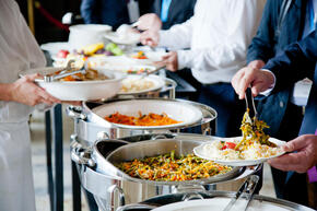 People use tongs to take food from catering trays in a hotel