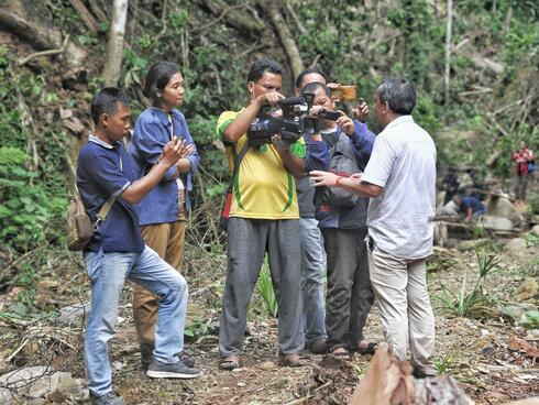 A group of people standing on a dirt road interview a man