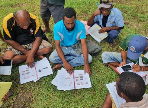 Men sit in a semicircle on grass looking at notebooks with fish images in them