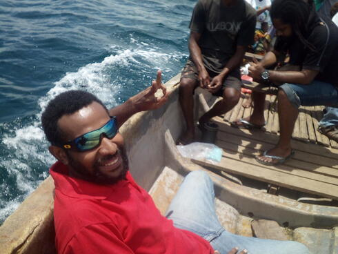 A man wearing sunglasses and a red shirt smiles at the camera while sitting in a small wooden boat on the ocean