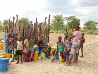 Members of the Kapau community sit on buckets used to transport water and look at the camera.