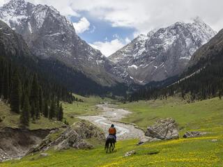 A horseback rider rides through the mountains