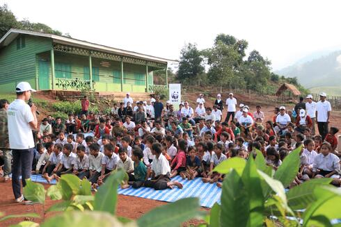 Local community members in Laos sit on blankets in the village common area laid out to discuss a tree planting and forest management program