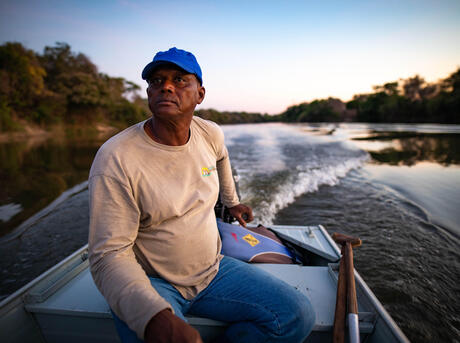 man traveling by boat down a river in Brazil