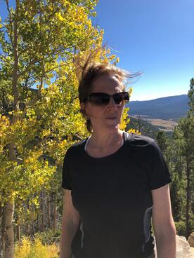 Margaret Ackerley in athletic clothing stands outside on top of a mountain during the fall season. A tall tree with bright yellow leaves is behind her.