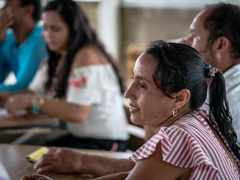Marisela Silva Parra, secretary of a group of local 'environmental promotors' sits at a table at a meeting
