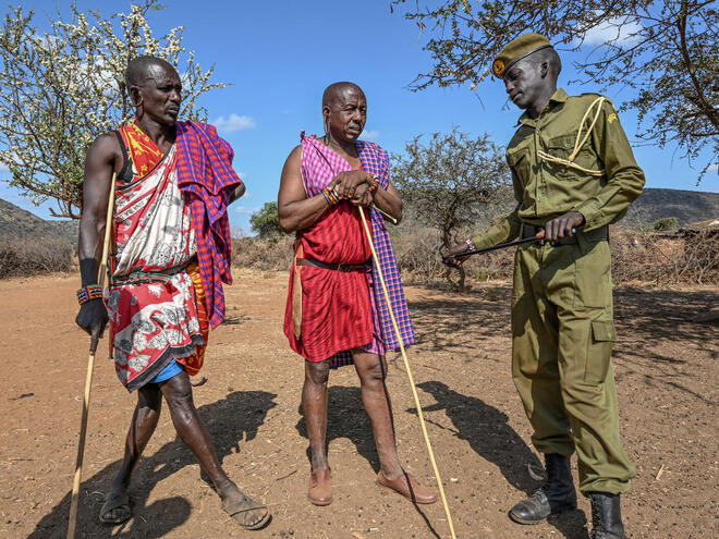 Community ranger Musa stands with two community members outside in a village in Kenya